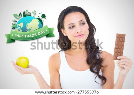 Pretty brunette deciding between apple and chocolate against white background with vignette - stock photo