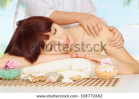 Pretty brunette doing massage at the spa - stock photo