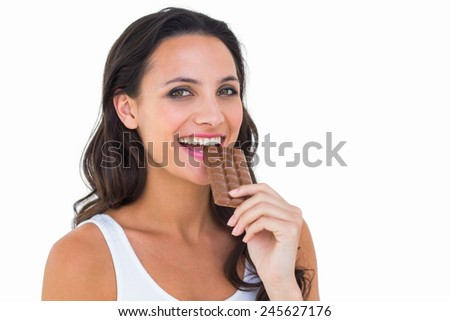 Pretty brunette eating bar of chocolate on white background - stock photo
