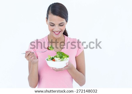 Pretty brunette eating bowl of salad on white background - stock photo