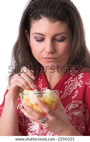 Pretty brunette eating from a bowl of fruit on white background - stock photo