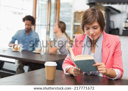 Pretty brunette enjoying her coffee with a book at the coffee shop - stock photo