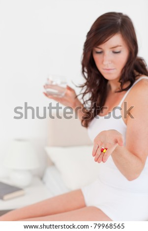 Pretty brunette female taking some pills while sitting on a bed - stock photo