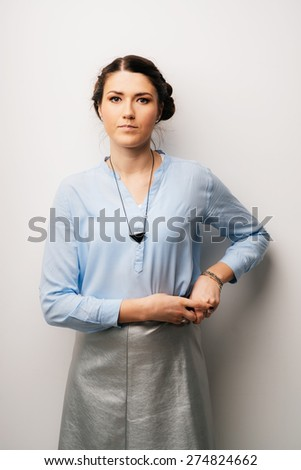 Pretty brunette girl angry hands on hips - stock photo