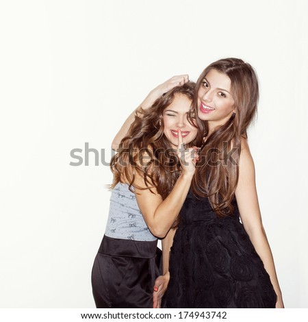 Pretty brunette girl friends having fun. One hugging other. Looking at camera and smiling. Inside - stock photo