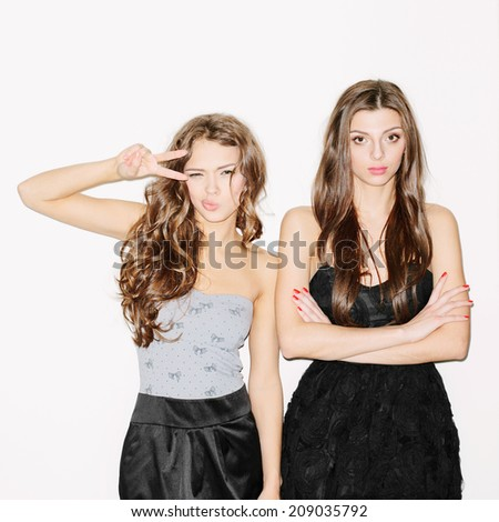 Pretty brunette girl friends having fun. One showing sign with her hand. Other looks serious. Festive mood. Inside