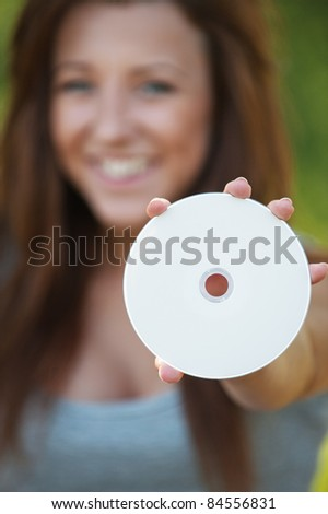 Pretty brunette girl holding compact disc at summer green park.