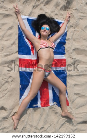 Pretty brunette girl in bikini lying on the Union Flag on the sand beach, view from above - stock photo