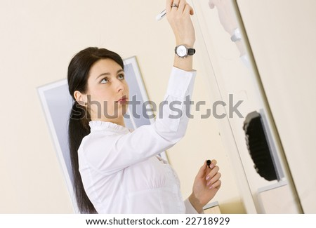 Pretty brunette girl making presentation in the office - stock photo