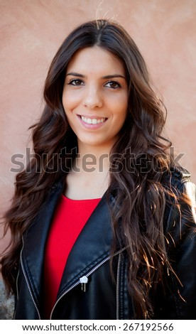 Pretty brunette girl smiling with leather jacket - stock photo