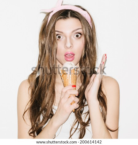 Pretty brunette girl wearing headband and eating ice cream. Looking surprised. Indoors, lifestyle - stock photo