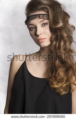 pretty brunette girl with long wavy shiny hair and stylish make-up wearing black summer dress and looking in camera  - stock photo