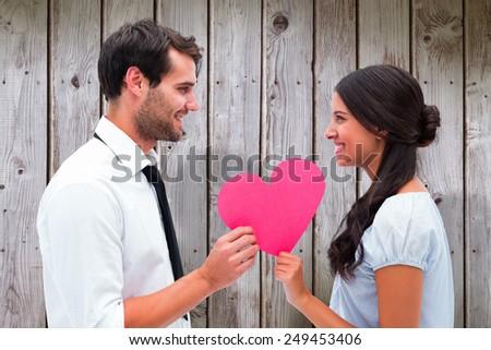 Pretty brunette giving boyfriend her heart against wooden planks - stock photo