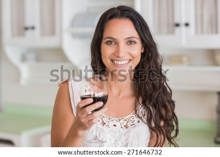 Pretty brunette having a glass of wine in the kitchen - stock photo
