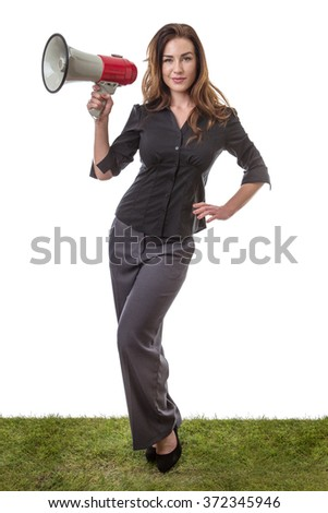 Pretty brunette holding a loud speaker in a business suit, standing on grass isolated on white