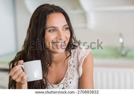 Pretty brunette holding a mug in the kitchen