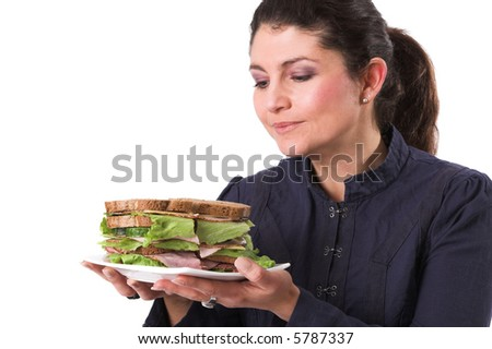 Pretty brunette holding a plate with a very healthy sandwich in her hands