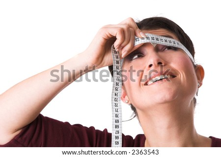 Pretty brunette holding the measuring tape around her head and trying to look at the numbers - stock photo