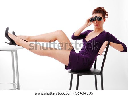 Pretty brunette is sitting on chair isolated on white. Her slender legs are lifted on the table. She is watching on binoculars. She is wearing short slinky dress and black pumps with high heels. - stock photo