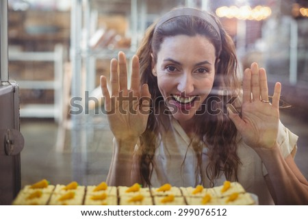Pretty brunette looking at pastries through the glass in the bakery store - stock photo