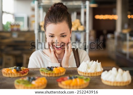 Pretty brunette looking at tarts at the bakery - stock photo