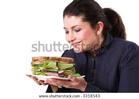 Pretty brunette looking forward to start eating her lovely healthy sandwich - stock photo