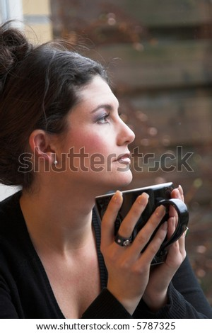 Pretty brunette looking out of the window holding a cup of tea