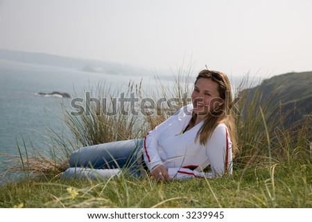 Pretty brunette lying on top of a cliff enjoying the sunshine and the views