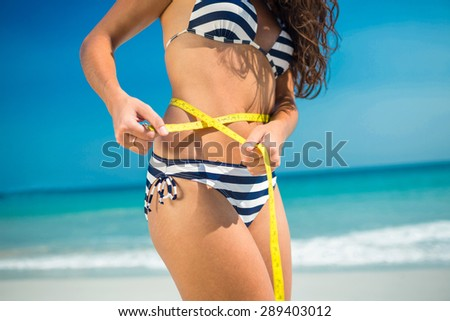 Pretty brunette measuring waist with tape measure at the beach - stock photo