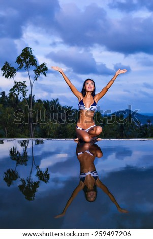 Pretty brunette model in blue striped bikini posing at the pool with reflection of the evening sky - stock photo