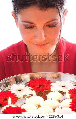 Pretty brunette over a bowl of floating candles and flowers - stock photo