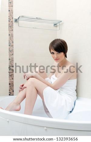 Pretty brunette posing in bathroom - stock photo