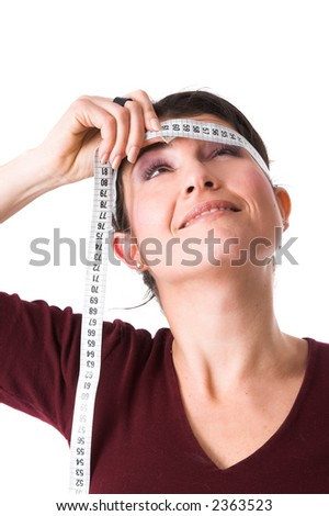 Pretty brunette putting the measuring tape around her head and peering upwards to see if there is any change