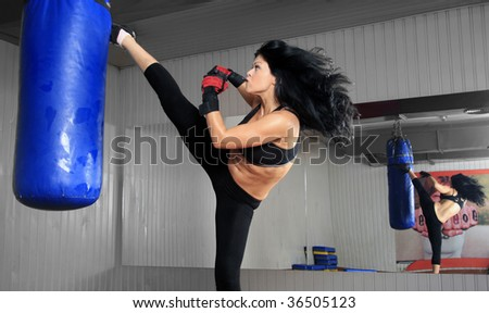 Pretty brunette ready to kick on white background - stock photo