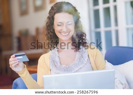 Pretty brunette relaxing on the couch with laptop in the living room - stock photo