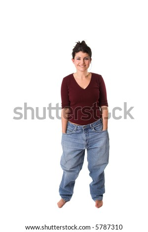 Pretty brunette showing off how much weight she has lost by putting on an old pair of jeans - stock photo