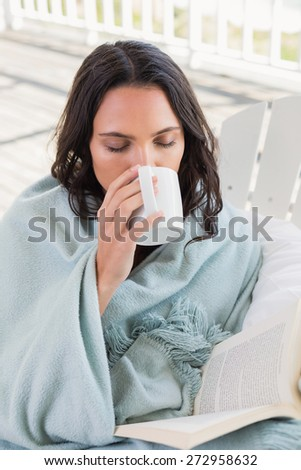 Pretty brunette sitting on a chair and drinking coffee in patio