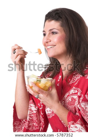 Pretty brunette snacking from a bowl of fruit - stock photo