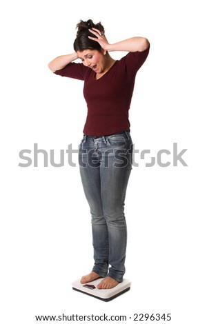 Pretty brunette standing on the scale and looking shocked at the results - stock photo