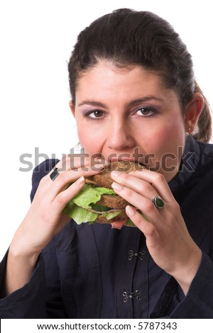 Pretty brunette taking a bite out of her healthy sandwich - stock photo