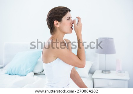 Pretty brunette taking her inhaler at home in the bedroom - stock photo