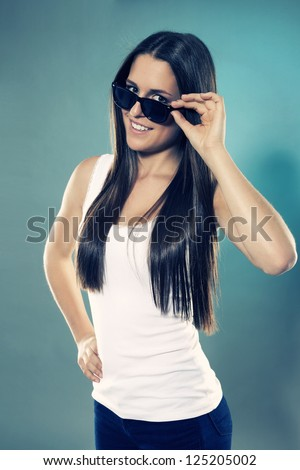 pretty brunette teenager looking over her black sunglasses - stock photo