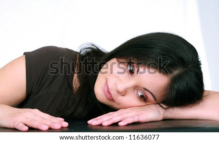 pretty brunette teenager with big eyes with head on hand - stock photo
