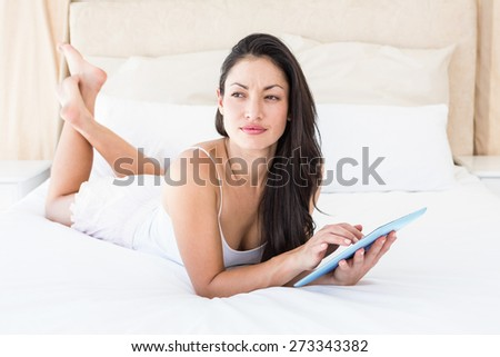 Pretty brunette touching tablet computer on couch at home - stock photo