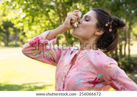 Pretty brunette using her inhaler on a summers day - stock photo