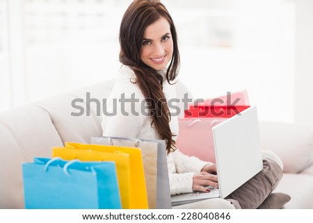 Pretty brunette using her laptop on the couch at home in the living room - stock photo