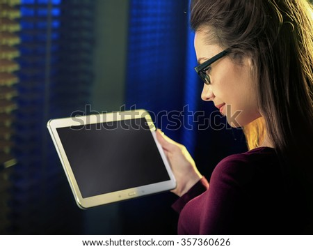 Pretty brunette using tablet at the evening