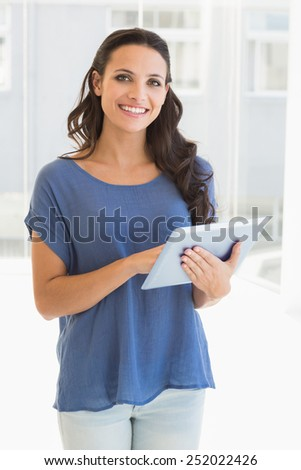 Pretty brunette using tablet pc at home beside window - stock photo
