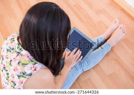 Pretty brunette using tablet sitting on the floor at home - stock photo