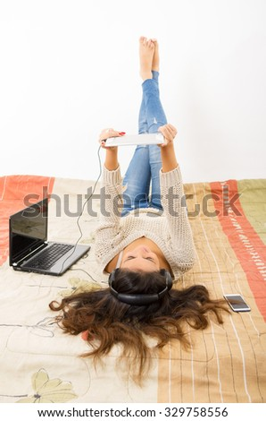 Pretty brunette wearing denim jeans white top lying down on bedsheets daydreaming with smartphone, laptop and tablet. - stock photo